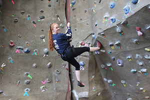 female student on the rock climbing wall with safety harness