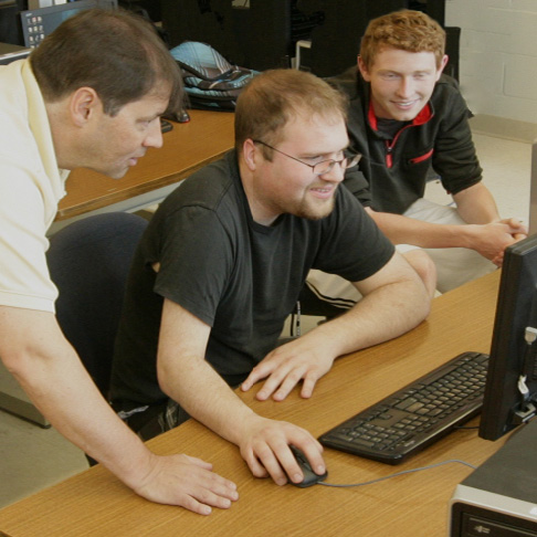 Three men at computer