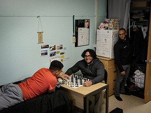 three male students in a residence hall, 2 playing chess