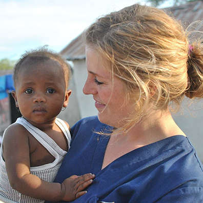 nursing student holding a baby in Haiti