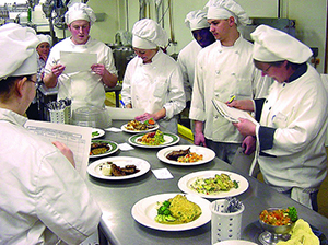 several culinary students in uniform standing around a table of plates