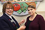 Sara Weller, accounts payable clerk, receives her commemorative 70th anniversary pin from ACES Director of Human Resources Christina Loper.