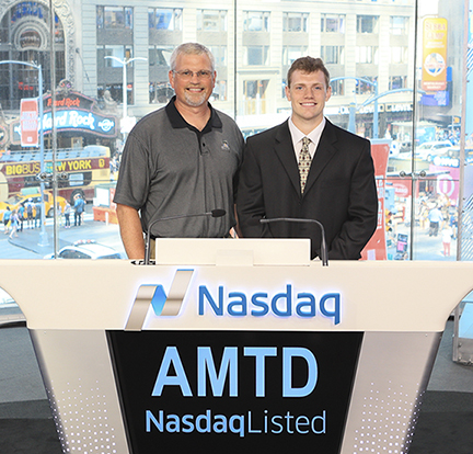 Adam Wilkins with his dad in front of Nasdaq podium, Times Square can be seen thru the window in background