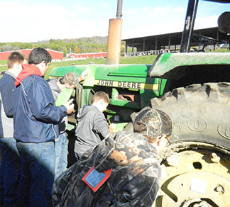 students around a green tractor at 28th annual Agriculture Skills Contest