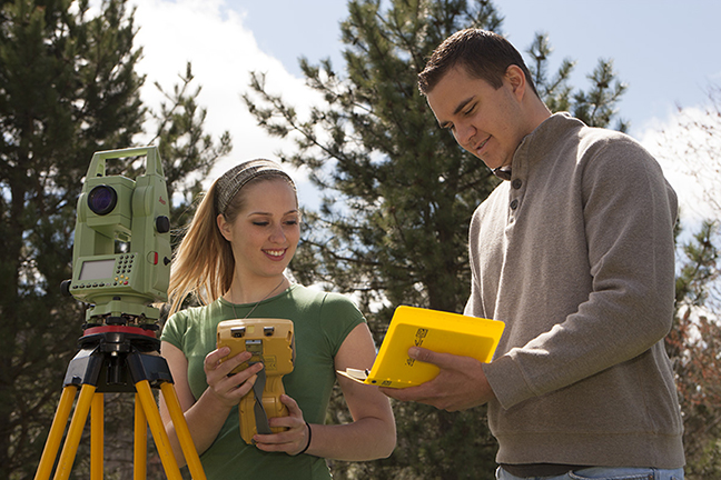 two students outside with survey equipment