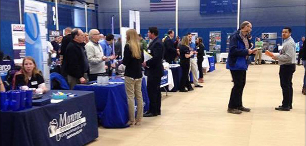 employers and students at tables in the gymnasium