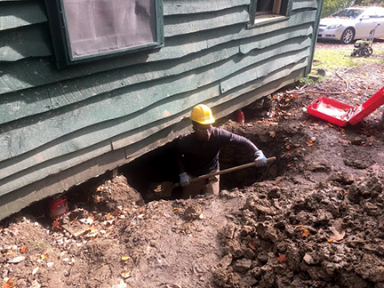 student wearing hard hat digging a hole underneath the house