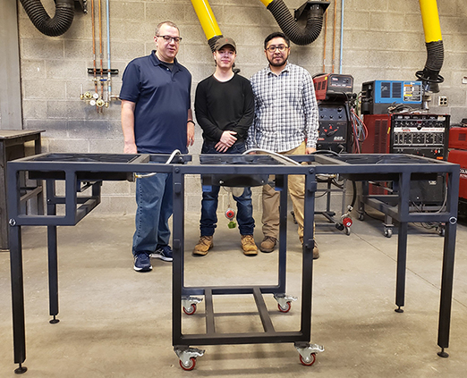 three males standing in front of a metal stand