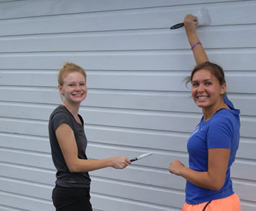 two female students holding paint brushes