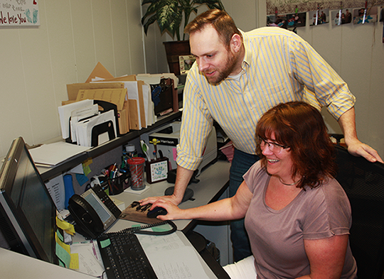 James Reese and Kelly Harrison at a computer and desk