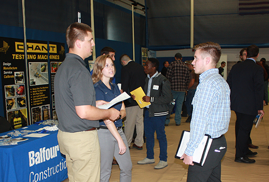 student holding notebook speaking with employer standing at a table at Career Fair in the gymnasium