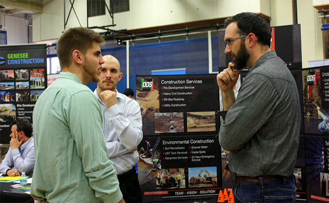 student speaking with two men at career fair