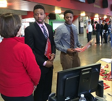 male students speaking with female recruiter standing near a table