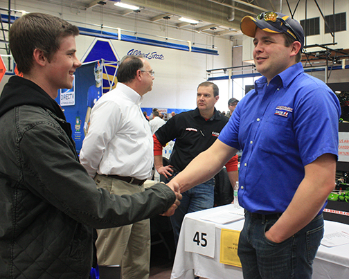 representative from Lamb & Webster Inc. shakes hands with a student
