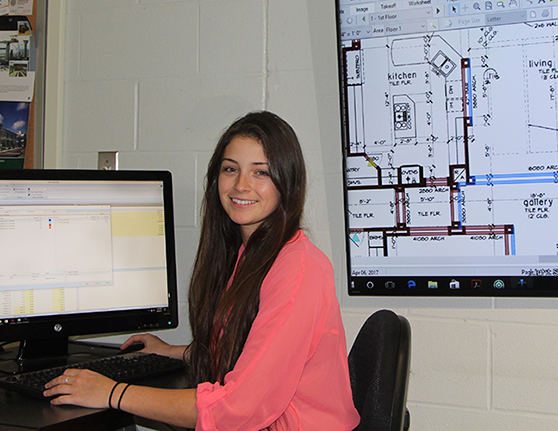 Carina Scalise sitting at a computer, interior diagram hanging on the wall