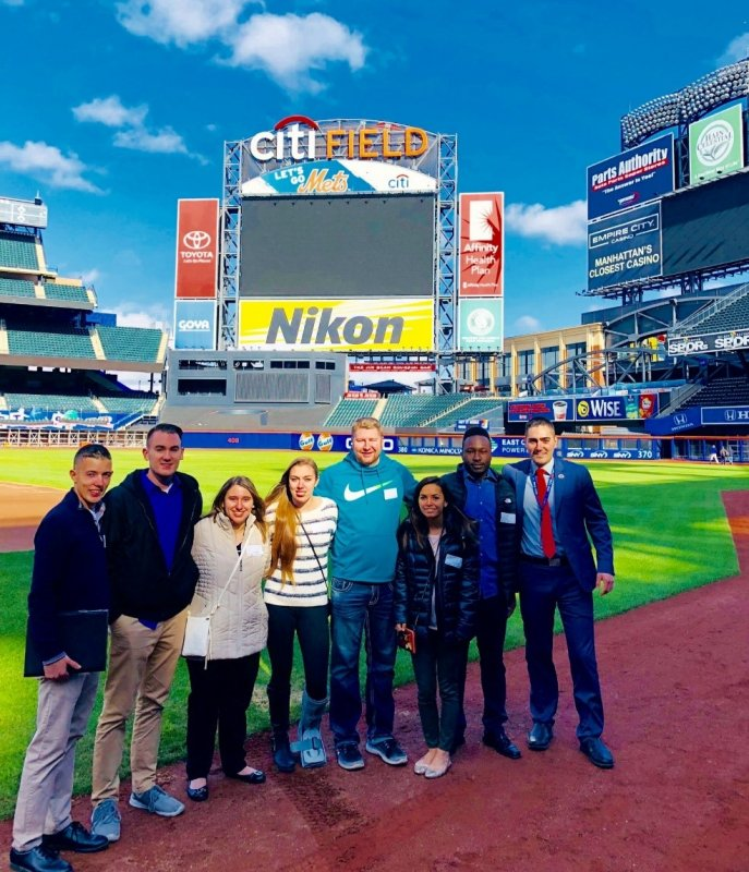 students standing in front of scoreboard at Citi Field