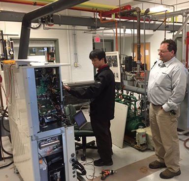 Yanmar engineers Yoshinori Jodo, left, and Michael Alfano inspecting the installation of the micro combined heat and power (Micro CHP) system