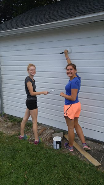 two girls painting the side of a white building