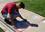 student drawing on sidewalk with chalk