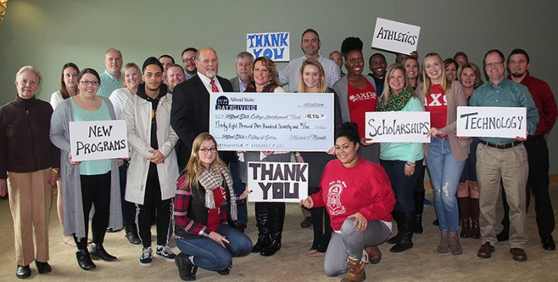 Students, faculty, and staff presenting a check and holding up Thank You signs