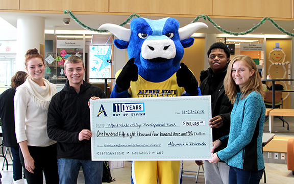 mascot holding a big check surrounded by students