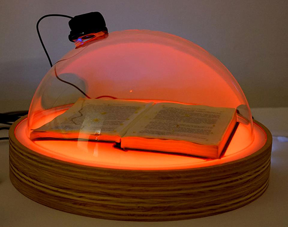 an open book under a piece of glass with a red light shining on it
