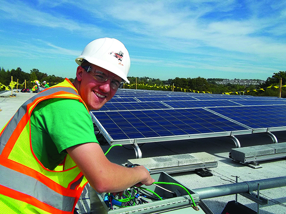 student wearing a hard helmet next to a solar panel