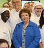 Evelyn Turner surrounded by students wearing their white culinary uniforms and hats