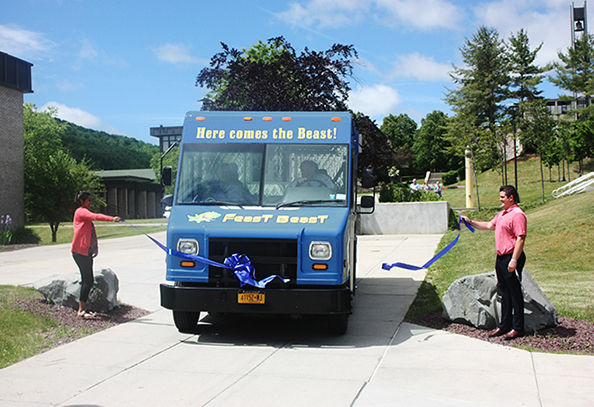 "President Dr. Skip Sullivan drives the new ""Feast Beast"" food truck through a ribbon during a ceremony"
