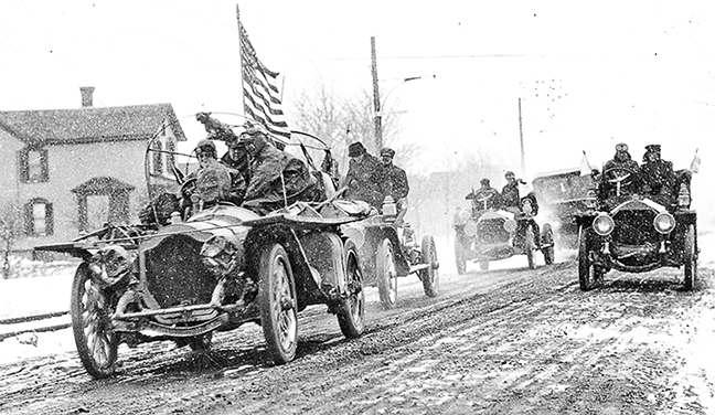 people driving old cars on a dirt road, american flag