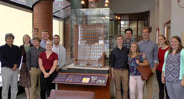 Associate Professor David Carli, left, and the students who constructed the model, standing next to the model