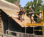 students working on the roof of a house