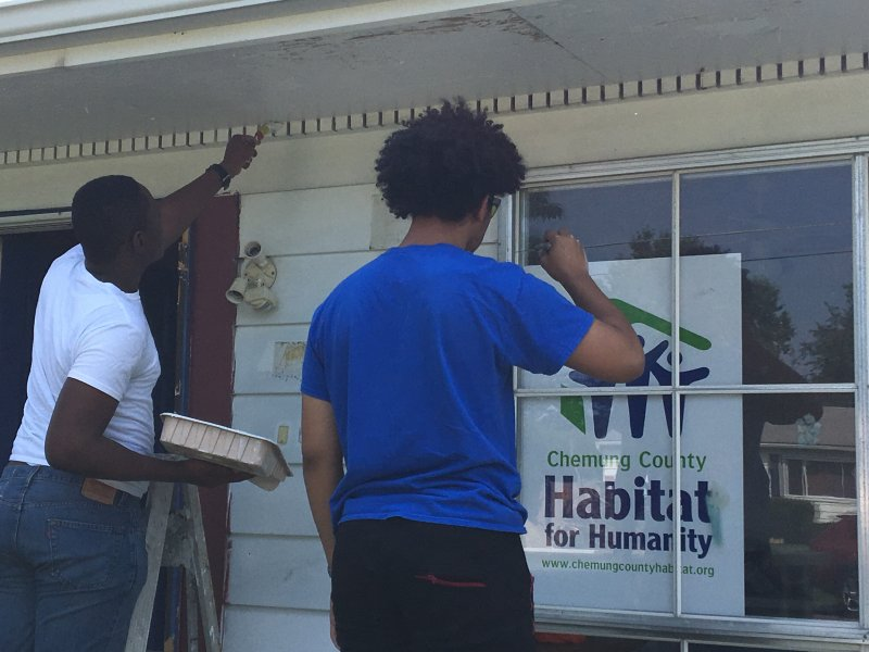 students painting front of a house, Habitat for Humanity sign in the window