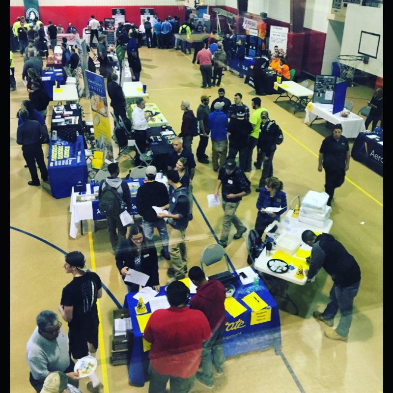 many students speaking with employers at the career fair in the gymnasium