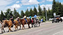 several people riding horses down a highway, cars behind them