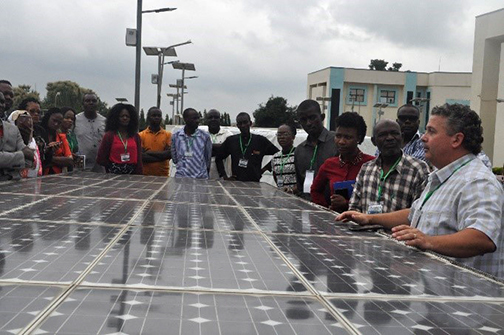 Jeffrey Stevens with group of people in front of a large solar panel