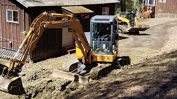 student operating a bulldozer in front of a cabin