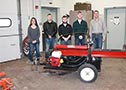The students stand behind the log splitter they helped create.