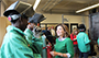 students in green uniforms and welding helmets and Lt. Gov. Kathy Hochul