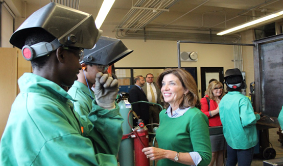 Lt. Gov. Kathy Hochul tours Burgard High School; students in green uniforms and welding helmets and Lt. Gov. Kathy Hochul