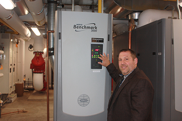 Senior Director of Facilities Services Glenn Brubaker poses with a new energy efficient satellite boiler