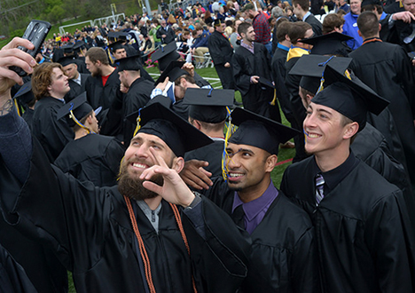 three male students at Commencement taking a selfie