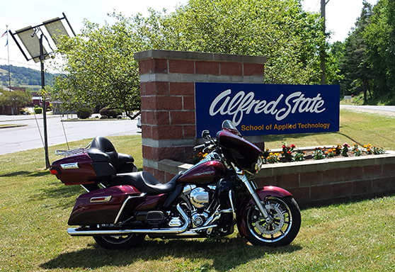 motorcycle in front of Alfred State sign on Wellsville campus
