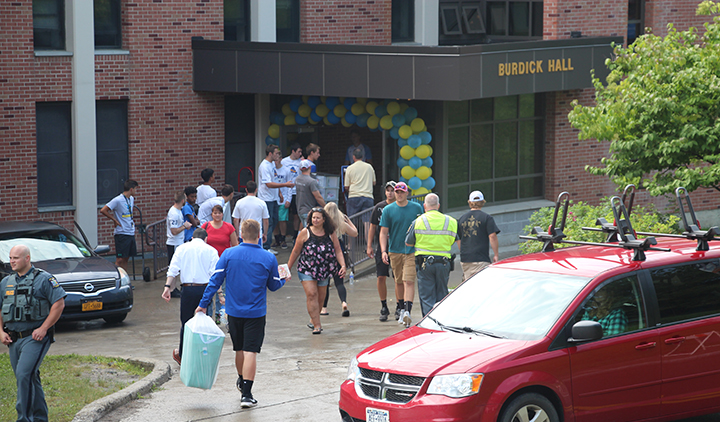 red van, people moving items into Burdick Hall, yellow and blue balloons