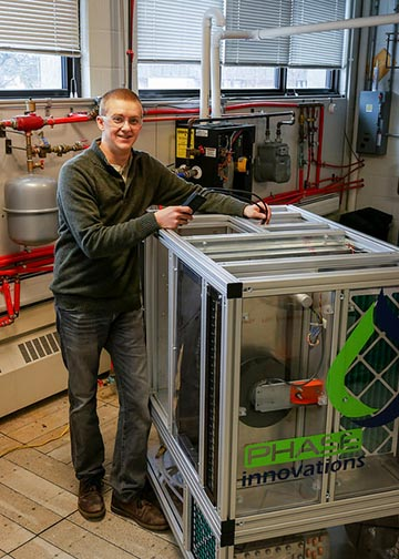 Nathan DeMario standing next to the cooling system
