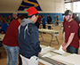 Zachary Herrington assists students with a National Engineers Week design challenge.