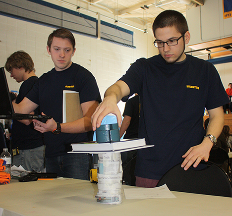 Alex Surdyk, an electrical engineering technology major from Hamburg, right, judges one of the entries in the design challenge that was part of Friday's National Engineers Week event.
