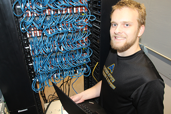 student standing in front of a bunch of blue wires
