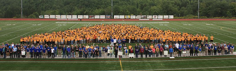 students, faculty, and staff in Pioneer Stadium create a human Alfred State logo