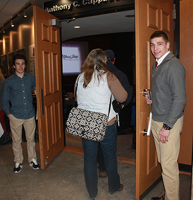 students Casey Connor (business administration, Cotuit, MA) left, and Ian Van Valen (construction management, Ithaca) hold open the doors to the Orvis Activities Center Cappadonia Auditorium